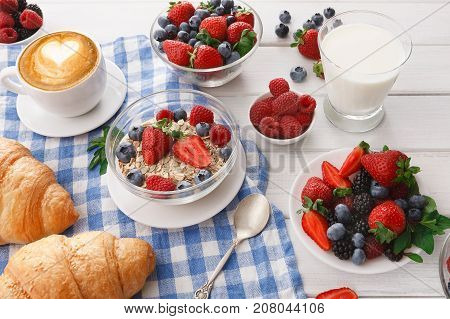 Rich continental breakfast. French crusty croissants, muesli, glass of fresh milk, cup of hot black coffee and lots of sweet berries for tasty morning meals. Delicious start of the day