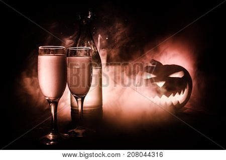 Two Glasses Of Wine And Bottle With Halloween - Old Jack-o-lantern On Dark Toned Foggy Background. S