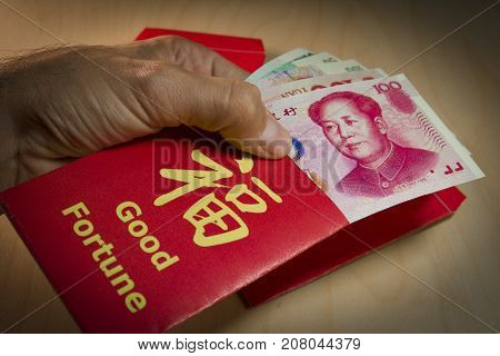 The red envelope or hong bao is used for giving money during the Spring Festival, or Chinese New Year in China and Taiwan. Envelope with the chinese words meaning Good fortune on it, and Yuan bills