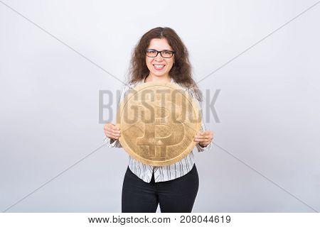 Business woman holding a Golden Bitcoin. Virtual money