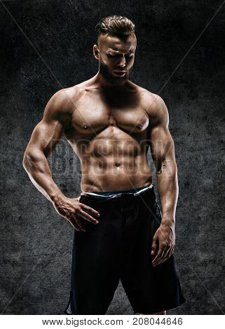 Man showing off his muscular physique. Photo of man with perfect body after training. Strength and motivation