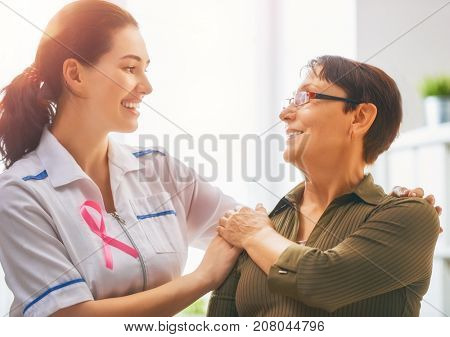 Pink ribbon for breast cancer awareness. Female patient listening to doctor in medical office. Raising knowledge on people living with tumor illness.