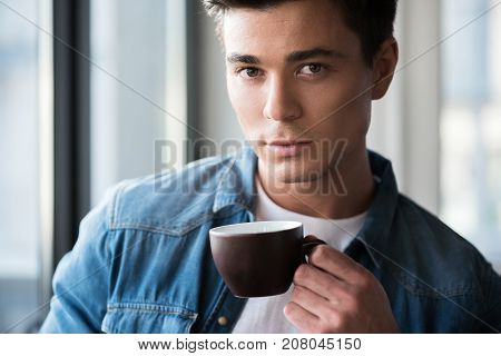 Deserved rest. Portrait of charming serious young man is drinking hot espresso and looking at camera thoughtfully