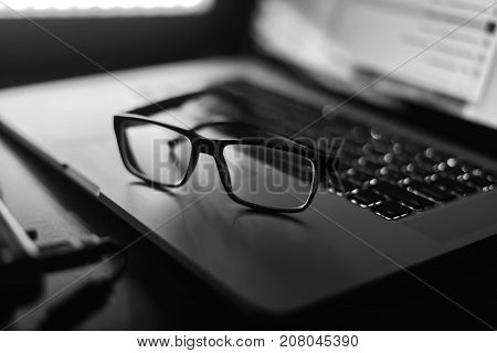 Illuminated glasses and a laptop on the table black and white poster