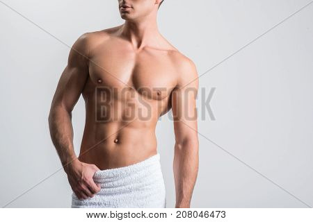 After shower. Close-up of muscular torso of young confident shirtless man is standing with towel on his hips. He is looking aside confidently. Isolated background with copy space in the right side
