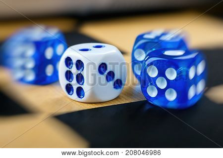 closeup shot of blue and white dices on chessboard with blur effect