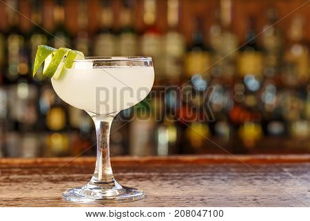Daiquiri cocktail with rum and lime juice. Traditional taste. The cocktail is on the bar in a pub or restaurant. Space for text.