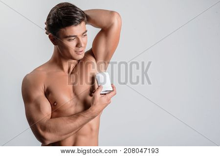 Daily care. Young positive naked man is applying antiperspirant under his arm to prevent perspiration with smile. Isolated background and copy space in the right side