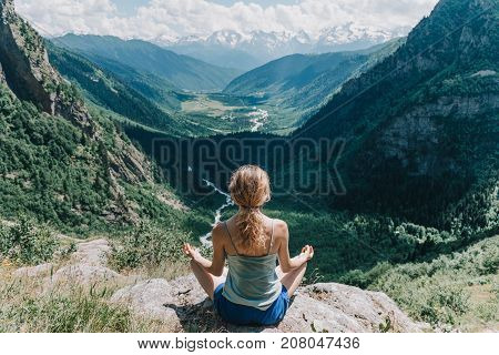 young girl meditates in the Lotus position on a background of mountains