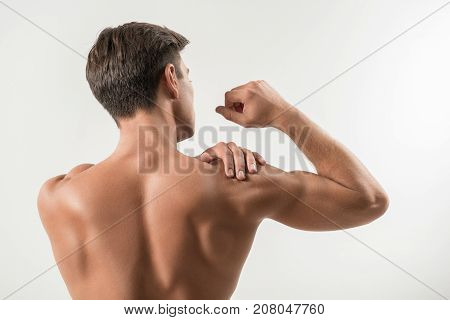 Ligament injury. Rear view of muscular young man is standing and feeling pain in his shoulder while massaging it. Focus on his naked back. Isolated background