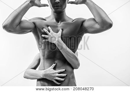 Desire. Close-up of sexual body of young man who is standing with raised hands. Female hands are hugging his torso with passion. Isolated and black-and-white