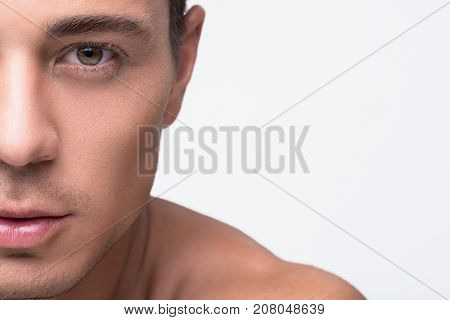 Close-up of half of face of fascinating young guy with naked shoulders. He is looking at camera thoughtfully. Isolated background and copy space in the right side