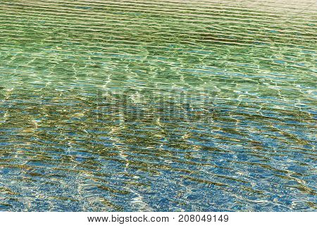 Refraction of light in clear water with small waves. Toned photo