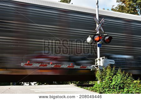 An image of a speeding train at a railway crossing.