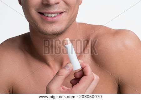 Close-up of hygienic lipstick in hand of positive young naked man. He is expressing gladness while holding balm. Isolated background. Beauty concept