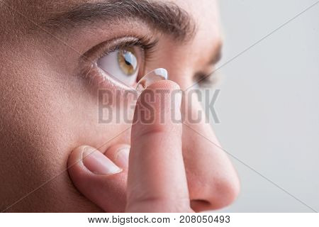 Eyesight and ophthalmology concept. Close-up of finger of young man who is putting contact lens in his eye. Isolated background