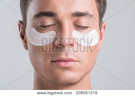 Rejuvenating procedure. Close-up portrait of young pleasant man with closed eyes is posing with sheet mask around his eyes. He is feeling relaxed. Isolated background