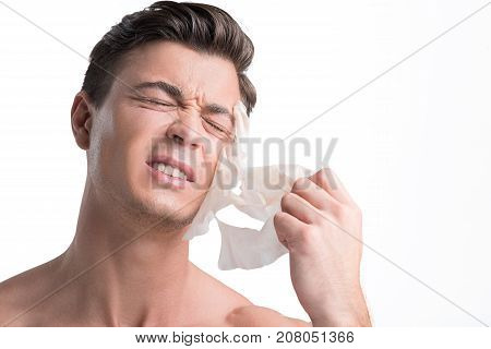 Skin care cosmetics and health concept. Close-up of face of young man who is removing facial mask sheet. He is expressing pain and unpleasant sensation. Isolated and copy space in the right side