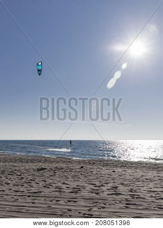An unrecognizable bold kitesurfer ride on sea water on a board with a blue kite in the bright light of the evening sun and glare on the water