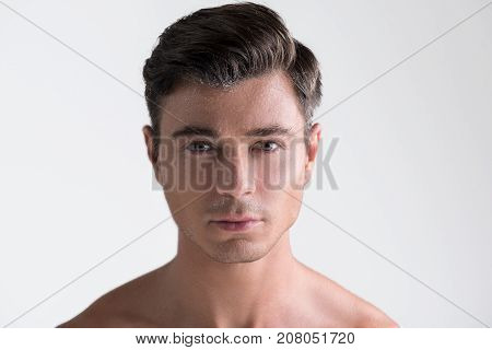 Male beauty. Close-up portrait of attractive young naked man with sweat on face. He is looking at camera with confidence. Isolated background