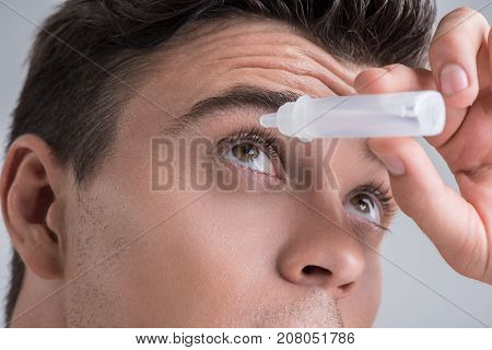 Care of eyesight. Close-up of face of young pleasant guy is using medical product for his eyeball. Isolated background