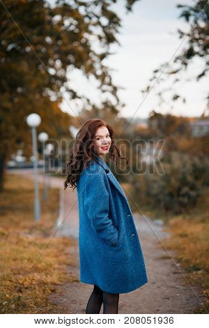 Romanric picture of fashionable young curly woman in autumn in park smiling and turning wearing blue coat. Girl turned with fluttering hair.