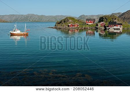 Small norwegian wooden houses and boat near Honningsvag Norway