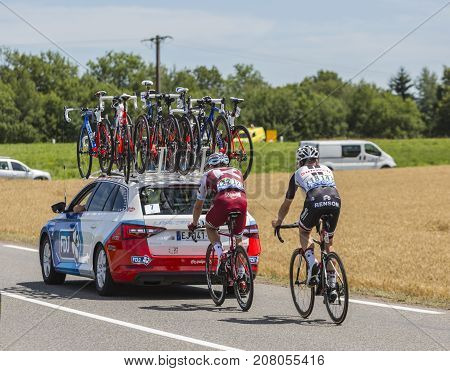 Mailleroncourt-Saint-Pancras France - July 5 2017: Rear image of two cyclists riding behind a technical car on a road to La Planche des Belle Filles during the stage 5 of Tour de France 2017.