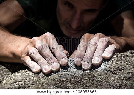 Man's hands climbing on granite. Italian Alps