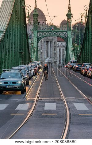 Front view of Liberty bridge in Budapest at sunset with cars in line and a male cyclist in the middle. Budapest, Hungary - September 27, 2017: Sunset perspective front view of Liberty bridge in Budapest Hungary with people in cars waiting in line in both
