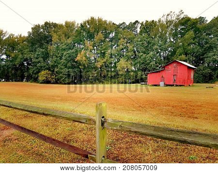 An old red barn out in a field near the woods. Copy space.