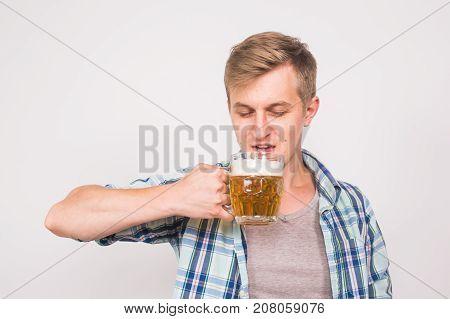 Man drinking beer. Happy young man holding a beer mug.