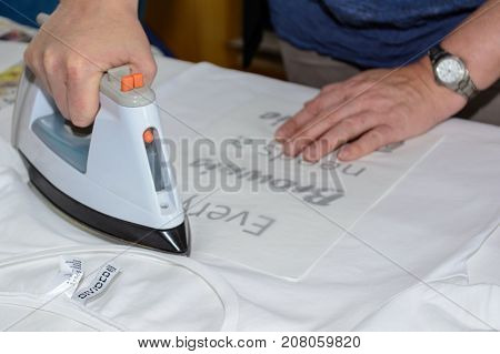 Person is ironing a text as a foil overprint on a t-shirt