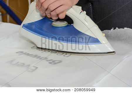 Person ironing an ironing sheet on t-shirt - close-up
