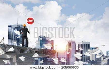 Rear view of engineer in helmet holding stop sign while standing among flying paper planes on broken bridge with cityscape and sunlight on background. 3D rendering.