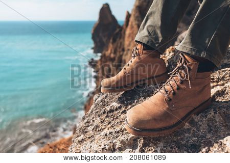 Man traveler sitting on mountain, closeup photo of hiking shoes. Boots on feet over sea landscape.