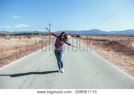 Hipster girl walking along the road, carefree and enjoying freedom and travel. Wanderlust concept scene.