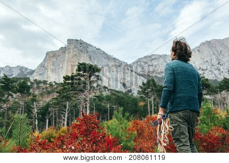 Back view of traveler man wearing sweater, holding rope and standing alone in autumn woods and looking at mountain hill. Cold weather, fall colors. Wanderlust concept.