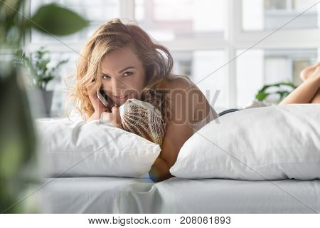 Girl is lying in bed and speaking on phone. She looking at camera with interest. Portrait