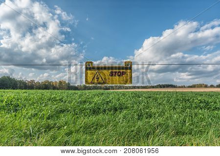 Picture of green field with blue sky and yellow warning sign.