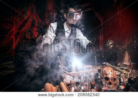 Scientist inventor steampunk works in his laboratory. Science fiction concept. Halloween.