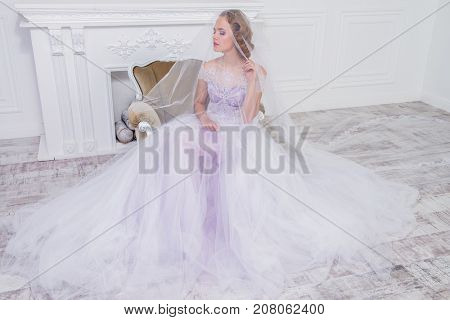 Charming bride woman in a beautiful wedding dress  with a lush skirt sits in armchair under the veil. Luxurious apartments.