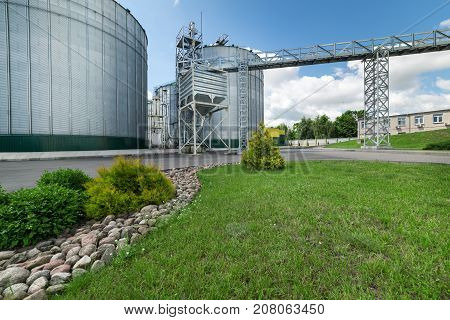 Large modern granary. In the foreground there is a luscious green grass, bushes and decorative masonry.