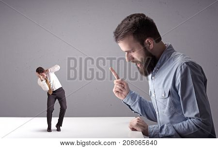 Young professional businessman being angry with an other miniature businessman in front of a splattered background