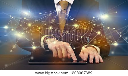 Businessman in suit typing with connection graphics around