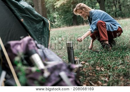Low angle of happy female tourist putting up a tent with joy in forest. She is kneeling in and smiling