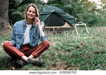 I am happy. Portrait of cheerful girl relaxing in camping. She is looking at camera and smiling. Copy space