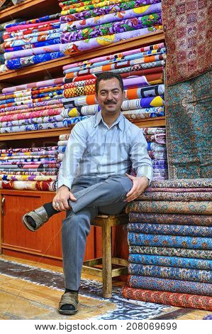 Fars Province Shiraz Iran - 19 april 2017: One Iranian textile trader sits on a chair near his goods in a fabric store.