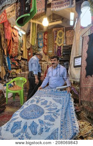 Fars Province Shiraz Iran - 19 april 2017: The department of decorative textiles in the city bazaar the Iranian seller demonstrates his goods.