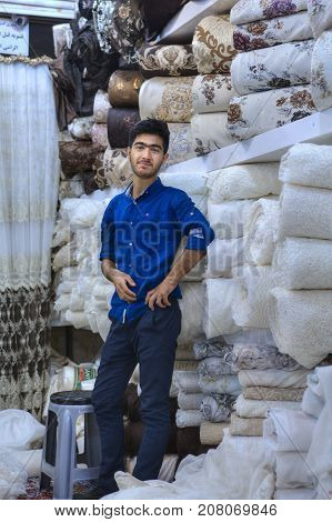 Fars Province Shiraz Iran - 19 april 2017: One young Iranian fabric seller is standing in a textile shop in the city bazaar.